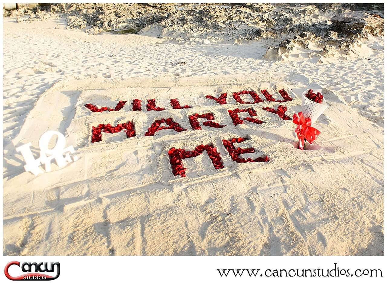 Will you Marry Me letters in th sand with Rose Petals